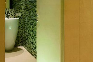 oben: Kugelküche und Essbereich werden durch den kubischen Funktionsschrank getrennt<br />links: Ein Blick ins Bad zeigt den Wechsel von Materialien der Oberflächen in den Nebenräumen<br />