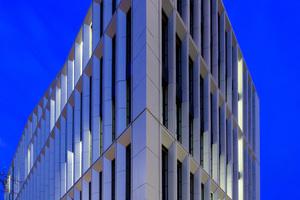 """<div class=""""10.6 Bildunterschrift"""">Als Fassadenmaterial wählte das Planungsteam Novelis ff2® mit dem 10500 m² realisiert wurden. Die einzelnen Fassadenelemente wurden dreidimensional gekantet und in den Tiefsicken verschraubt. An den großflächigen Fronten verlaufen die vertikalen Lisenen über zwei Etagen, die horizontalen erstrecken sich über die gesamte Breite des Gebäudes</div>"""