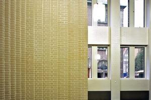 Eingang in die Kundenhalle, deren Wände mit hellen Riemchen verkleidet wurden. Sie erhält Tageslicht von zwei Seiten und wirkt damit hell und einladend