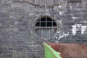 Hier wird das Fenster, knapp neben dem Adler, aus der Wand unterhalb der Treppe gebrochen