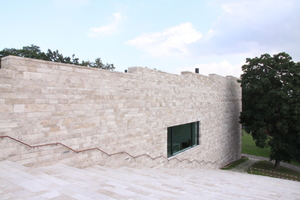 Der Naturstein Travertin, handwerklich geschichtet, bildet die Fassade des Gebäudes