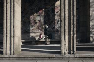 """Obdachlos in einer reichen Stadt: Ein junger Mann baut sein Nachtlager ab, das er vor dem Wandgemälde """"Der Tag"""" des Niederländers Jan Thorn Prikker aufgeschlagen hatte"""
