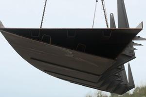 Der Stahl-Hohlkasten des Seilbrücken-Überbaus wurde in fünf Segmenten mit je 24m Länge im Werk vorgefertigt und auf die Baustelle transportiert. Die einzelnen Schüsse wurden auf bis zu 18m hohen Gerüstrahmen aufgelegt<br />