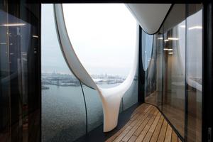 """Jedes Glasfassadenelement ein Unikat. Die """"Harfen"""" genannten Kunststoffelemente öffnen auch im Foyerbereich das Haus nach außen"""