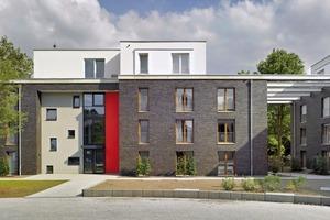 """<div class=""""9.6 Bildunterschrift"""">Leuchtend rote Farbfelder markieren die Eingangsbereiche auf der Innenhofseite</div>"""