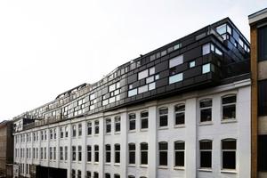 Straßenansicht: historischer Industriebau wird von zeitgenössischer Architektur geschickt beantwortet