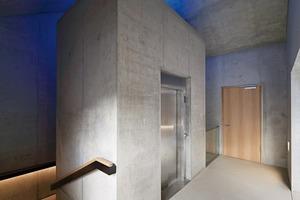Über ein skulpturales Treppenhaus gelangt man nach oben: Decken, Böden und Wände sind komplett aus Beton, selbst der Fahrstuhlkern und die dreiläufige Treppe