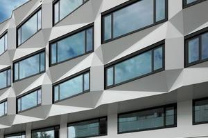 Dunkle Kastenfenster sind in die plastische Wabenstruktur aus weißen, leicht glänzenden Flächen eingelassen