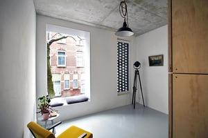 Zwei Fenstervarianten: ein tiefes Erkerfenster als Sitznische und ein schmaler Fensterstreifen hinter einem offenem Mauerwerksverbund–beides zum öffentlichen Straßenraum