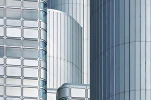 Die prägnante Aluminiumfassade ist optisch nahezu unverändert. 6000 Fassadenpaneele wurden gereinigt und in die neue zweischalige Elementfassade als Kastenfenster eingefügt. Unter und über den Glasfeldern strömt Frischluft über die kleinteilige Perforierung der Aluminiumpaneele in das Kastenfenster ein. Um während der Bauphase nie den Eindruck einer Großbaustelle zu erwecken, wurde die Fassade geschossweise nach einer ausgeklügelten Logistik ausgetauscht. Nur wenige Ebenen waren zeitgleich geöffnet, knapp 12 Monate wurden für den Austausch der Fassade benötigt