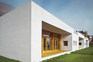 Eine Reminiszenz an die Engadiner Bautradition: Dicke Steinmauern, darin kleine Fenster, die sich in den tiefen Laibungen ducken. Die Haupträume öffnen sich bedarfsgemäß über die ganze Breite erst zur gedeckten Terrasse und dann zum Spielgarten