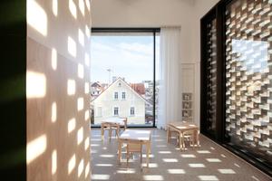 Kinderbibliothek mit großen Lese-, Turn-, Ruhemöbel (links). Rechts die Ziegellochfassade, die das auch in Wintertagen grelle Sonnenlicht angenehm filtert