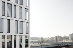Die Aluminium-Glas-Bandfassade nimmt über eine Agraffenkonstruktion die Lasten der GFB-Fertigteile auf