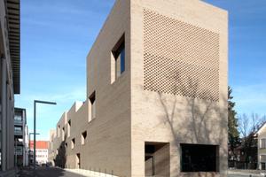 Südostansicht. Hier verbirgt das gelochte Ziegelmauerwerk die große Fensteröffnung in der Kinderbücherei. Unten links: Tiefgarageneinfahrt, rechts Schaufenster zum Café