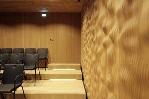 Die Oberfläche des Kleinen Saals besteht aus CNC-geschnittenen Eichenplatten, die zu einer ondulierten Oberflächenmatrix verleimt wurden. Akustisch wirksam und wie die Oberfläche im Großen Saal zum Anfassen verführerisch