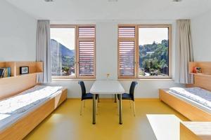 Tiefe Fensterbrüstungen ermöglichen den Blick in die Umgebung. In der Kinder- und Jugendpsychiatrie gestalten die Architekten die Einzel-, Doppel- oder Dreibett-Räume hell. Vor der Sonne schützen außenliegende, feststehende Holzlamellen