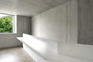 Die talseitige Wohnung erhielt einen versiegelten Betonboden. Das Treppengeländer der talseitigen Wohnung entwickelt sich zu einem Element, welches als Schreibtisch genutzt werden kann