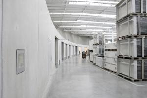 Anlieferung und Büroeinbauten auf der Innenseite der elf Meter hohen Wand aus Betonfertigteilen