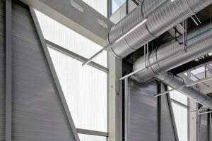 Glas und transluzentes Profilbauglas sowie der das Tageslicht reflektierende, hellgraue Boden sorgen für angenehme Arbeitsräume in der Produktionshalle