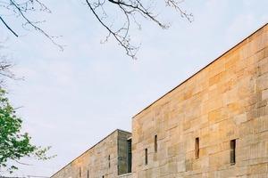 Drei verschiedene Höhen und zwei verschiedene Breiten der Grauwack-Platten wurden für die Mischkonstruktion von tragender Vorhangfassade und Mauerwerk in Maßarbeit hergestellt.