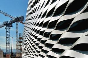 Als Fassadenmaterial wurden eloxierte, 3mm dicke, ca. 40cm breite einfach gekrümmte Aluminiumstreifen (einfache Vorfertigung) gewählt. Die Montage der insgesamt 15000 Wellenelemente vor der hochwärmegedämmten Gebäudehülle erfolgte mithilfe passgenau vorgefertigter Konsolbleche