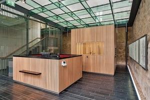 In das Foyer, dessen Hülle und Unterkonstruktion aus Glas bestehen, sind freistehende Betonkuben gestellt, die mit Holz verkleidet sind