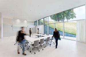 Der durch Schiebetüren flexibel gestaltbare Konferenzraum und das Forum als zusätzlicher Aufenthaltsbereich liegen direkt an der Glasfront zum Schlossgarten