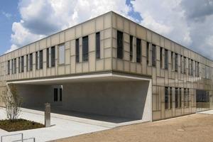 Der als Solitär ausgebildete liegende zweigeschossige Baukörper umschließt vier begehbare Innenhöfe und wird von einer transluzenten Hülle aus glasfaserverstärkten Kunststoffelementen bekleidet<br />