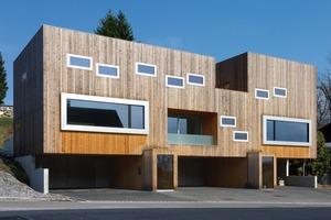 Foto1: Das Wohnhaus aus Holz ist 22m lang. Hier haben drei Familien ihr zuhause gefunden. Zwei große Panoramafenster zeigen die Wohnräume der größeren Familien an während die Wohnung der Tante in der Mitte platziert wurde. Nach außen erkennt man diese Wohnungseinheit an der tiefliegenden Loggia<br />