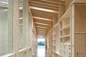 oben: Die sichtbare Holzkonstruktion und deren gleichmäßiger Rhythmus von Stützen, Trägern, Deckenbalken (hier nicht sichtbar) und Sparren bestimmt das Gebäudeinnere