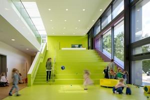 In dem zweigeschossigen Mehrzweckraum, dem Herzstück der Kita, lädt eine große Freitreppe mit knapp 35cm hohen Sitzstufen die Kinder nicht nur zum Hinsetzen, sondern auch zum Klettern und Erkunden ein