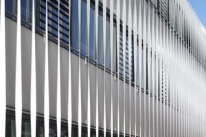Die Lamellenschicht besteht aus insgesamt 232 senkrecht angeordneten gedrehten Bändern, die teilweise als Sonnenschutz dienen. Außerdem leiten sie durch ihre gewundene Form Tageslicht ins Innere. Möglich wird dies durch die Oberfläche: In einem Nasslackierverfahren hat HD Wahl als Spezialist für die Beschichtung von Aluminiumbauteilen die Lamellen im Farbton RAL 9016 beschichtet. Die glänzende, brillant weiße Oberfläche lässt die Struktur zart und filigran erscheinen und ermöglicht die starke Lichtabstrahlung
