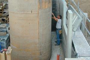 Die Stampflehmwände für das Treppenhaus schalten die Handwerker mit geschosshohen, an den Ecken abgerundeten Schaltafeln