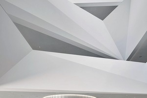 Im Hauptfoyer betonen eine Lichtfuge und die Materialauswahl die Vertikalität der runden Treppenhaustürme
