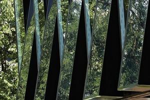 """<div class=""""13.6 Bildunterschrift"""">Die umlaufenden Stahlrahmen der keilförmig ausgestellen Fassadenelemente beträgt 36 mm. Sie sitzen vor den Geschossdecken, greifen über diese hinweg und lassen den Bau monolithisch erscheinen</div>"""