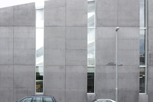 Der Fassadenausschnitt zeigt, dass hinter den Betonscheiben an der Sandstraße auch eine Terrasse über den Werkstätten im EG liegt (linke Bildseite)