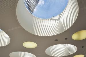 Zwölf kreisrunde Lichtkanonen mit bis zu 2,4m Durchmesser filtern Tageslicht auf die locker im Foyer verteilten Sitzinseln