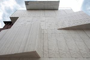 Robuste Fassaden- und Baukörperplastik hinter zartem Linienmuster