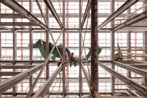 Für den Umbau wurde das Gebäude bis auf sein Stahlskelett komplett entkernt, um die geplanten Wohnungen unterzubringen. Die schlanken Außenwandstützen stehen in einem Raster von 1,8m. Zusammen mit den geschweißten Rahmen-ecken lassen sie die Konstruktion zwar engmaschig, aber filigran erscheinen. Sechs stärker<br />dimensionierte Mittelstützen bilden mit davon ausgehenden Unterzügen das innere Tragwerk