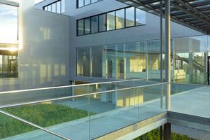 Die Vielzahl der horizontalen und vertikalen Sichtbezüge über große Glasflächen, die Atrien und das umgebende Grün hebt die Grenzen zwischen den Funktionsbereichen auf und spiegelt den Anspruch des Unternehmens nach Kommunikation und maximaler Transparenz wider