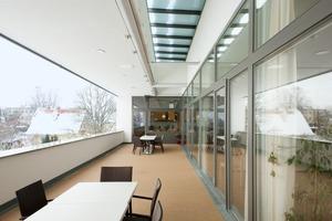 Glastüren sorgen für einen schwellenlosen Übergang auf die riesige Terrasse, In ihr Dach ist ein Oberlichtband geschnitten, das sich mit Jalousien beschatten lässt