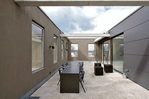 Die Dachterrasse ist von der Fassade eingefasst, so dass der Kubus von außen sein Erscheinungsbild bewahrt. Um vor Wind zu schützen, sind Verglasungen in den Öffnungen