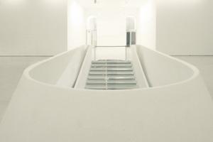 """Nach dem Abstieg vom Foyer gelangt man auf das alte Foyerniveau, von hier aus führt die mit kompakten, handgeschliffenen Betonwangen begleitete """"Showtreppe"""" ins Unterirdische hinab"""