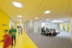 Die schuleigene Bibliothek ist im Erdgeschoss gegenüber der Verwaltung angeordnet. Sitzmöbel bieten Treffpunkte für Schüler und Lehrer