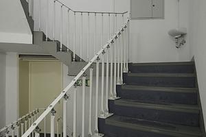 Nebentreppenhaus mit skuriler Handlaufkonstruktion und Waschbecken auf dem Absatz