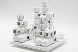 Kapselhäuser, Solingen-Caspersbroich, nicht realisiert, Modell 1969 Architekt: Wolfgang Döring, Düsseldorf Um den Bauherrn vom gewünschten Entwurf des Bürogebäudes Point West Place zu überzeugen, brachte der Architekt zu einer Besprechung ein Miniaturschränkchen aus Karton mit sieben Wüsste man nicht, dass es sich um den Entwurf für eine Wohnanlage handelt, könnte man die Stapel aus 57 Kunststoffelementen für eine abstrakte Skulptur oder ein Spielzeug halten. Das modulare Bausystem aus gleichartigen und vorfabrizierten Wohnkapseln ist im Präsentationsmodell in reiner Form umgesetzt; die vertikale Erschließung durch Wendeltreppen ist nicht dargestellt.