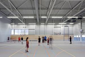 Ganz oben befindet sich die unterteilbare Sporthalle, deren Stahlkonstruktion wie ein Tisch auf die Stahlkonstruktion des Schwimmbades gestellt ist