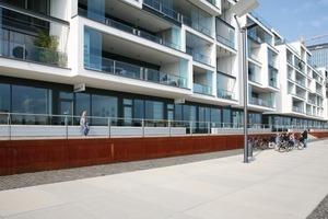 Großformatige Betonplatten, Kopfsteinpflaster, Cortenstahl als Wandung der Höhenversprünge und überbreite Sitzbänke prägen die Außenbereiche