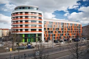 """Der verbindende Kopfbau """"Apels Bogen"""" mit Verwaltung und Wohnen belebt die Einheitsplatte hinter ihm. Ablesbar sind die unterschiedlichen Nutzungen. Orangetöne kehren auch in den sanierten Wohnbauten wieder. Die vorgestellten Balkone des Bestands zur Friedrich-Ebert-Straße erweitern die Wohnungen um einen Wintergarten"""