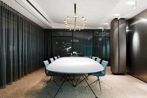 Am Ende des Ganges befinden sich Konferenzräume. Hochfloorige Teppiche, silberne Vorhänge, Regalwände aus metallisch wirkendem HPL schaffen eine konzentrierte Arbeitsatmosphäre<br />